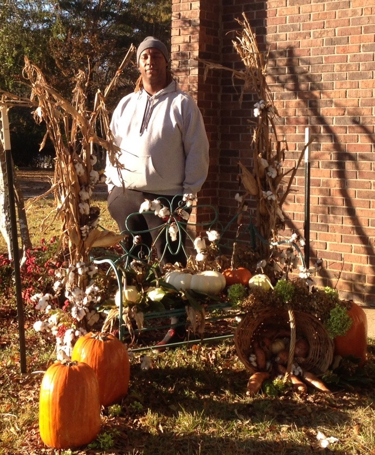 Picture of Danyel Armstrong behind fall decorations of pumpkins, cornstalks, and cotton which he designed.